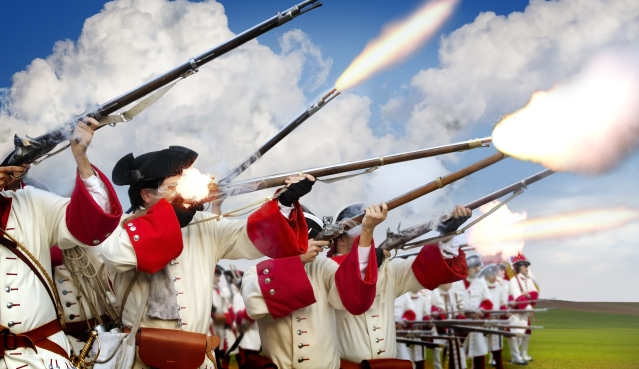 Soldiers of the American Revolution fire their bayonets into the sky during reenactment.