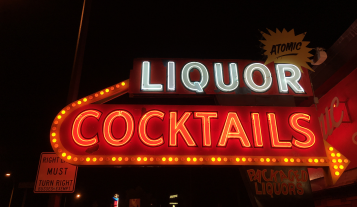 The historic Atomic Liquor sign glowing at night.
