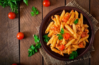 A dish of pasta garnished with fresh cherry tomatoes and basil.