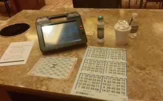 Vegas bingo machine with paper play, a dauber and a cocktail